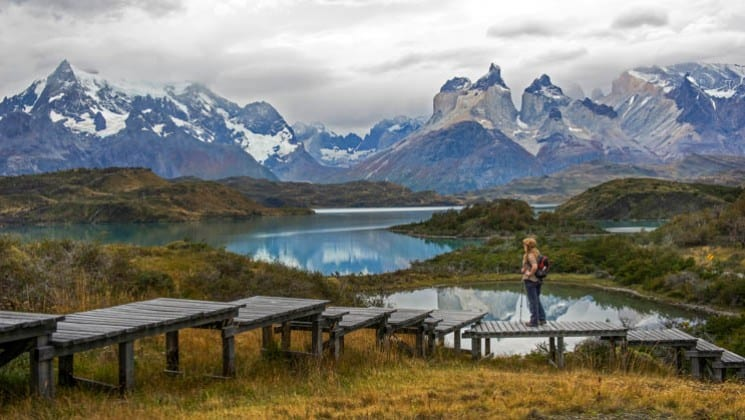 woman on boardwalk viewing lake and snow-covered mountains on explora patagonia land tour