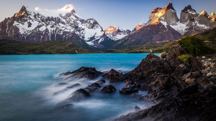 fog on the lake with snow-covered mountains on explora patagonia land tour