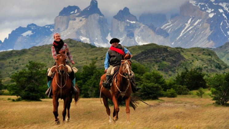 two horseback riders with snow-covered mountains in background on explora patagonia land tour