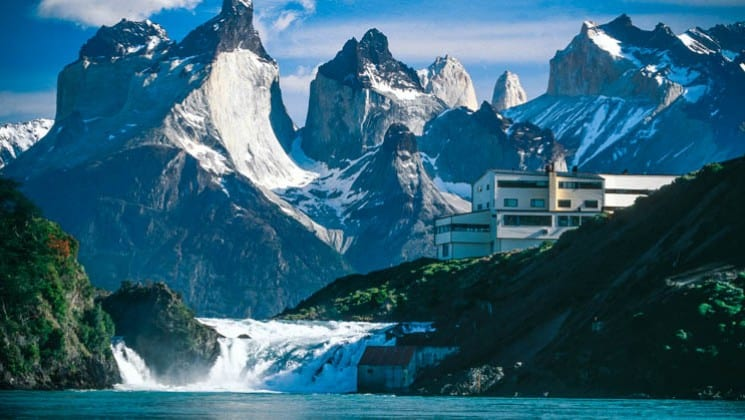 hotel next to waterfall and lake with snow-covered mountains on explora patagonia land tour