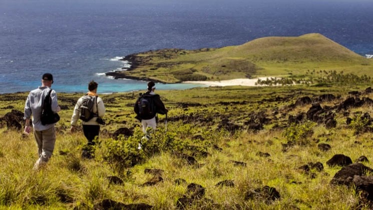 three hikers on coast of easter island on explora rapa nui land tour