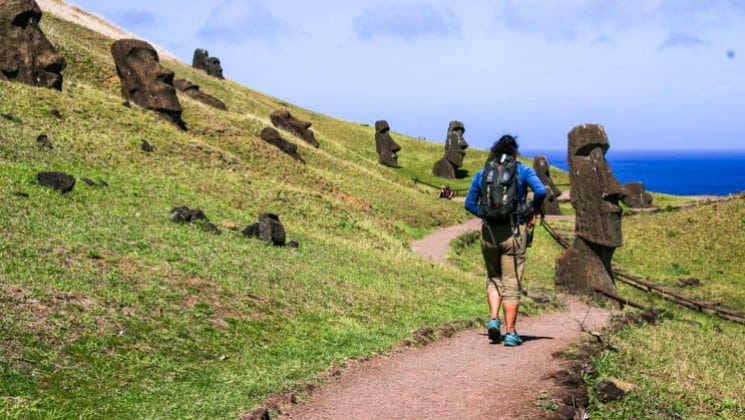 hiking trail on hillside with easter island statues on explora rapa nui land tour