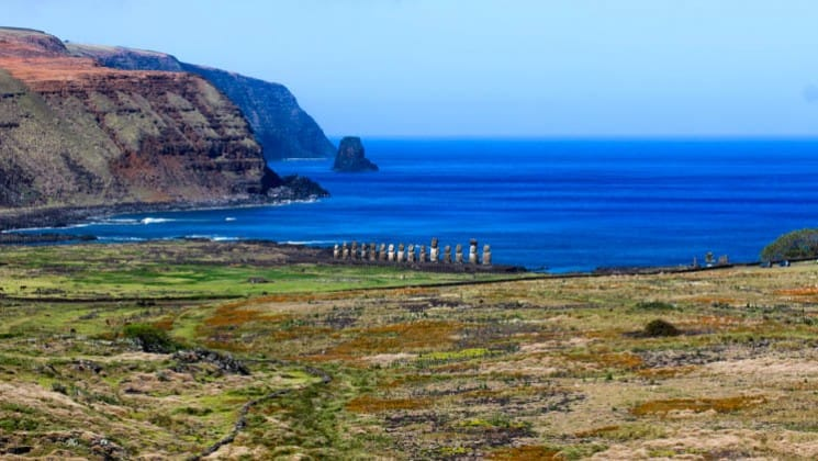distant view of easter island statues along ocean backdrop on explora rapa nui land tour
