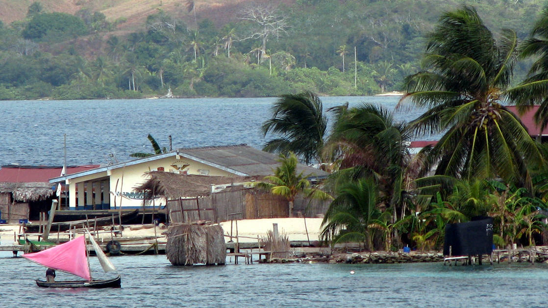 A small settlement of Guna Yala people on the ocean with a small sailing dingy with a red sail in Panama