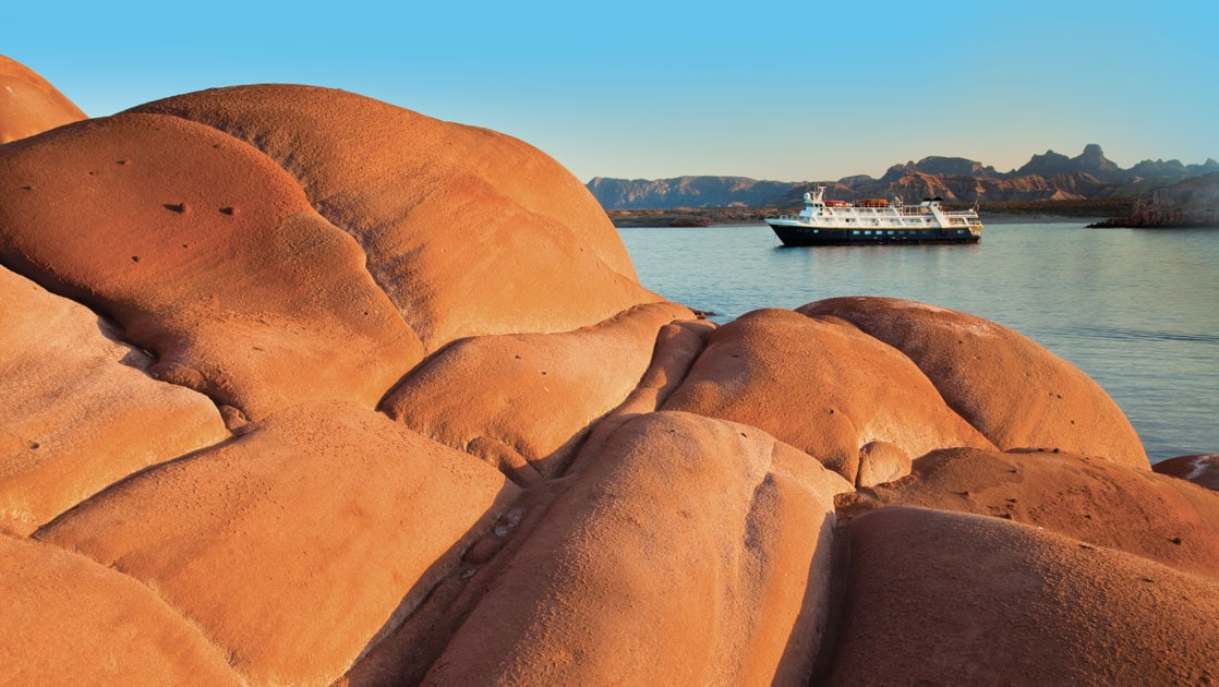 Sandstone rock in foreground with a small expedition ship in the background on a sunny day in Baja during a Sea of Cortez small ship cruise.