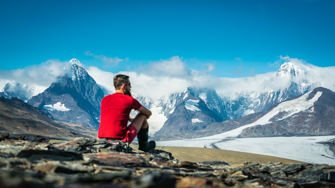Man in bright red shirt sits atop a mountainside, looking out over snowcapped peaks on a sunny day in Antarctica.