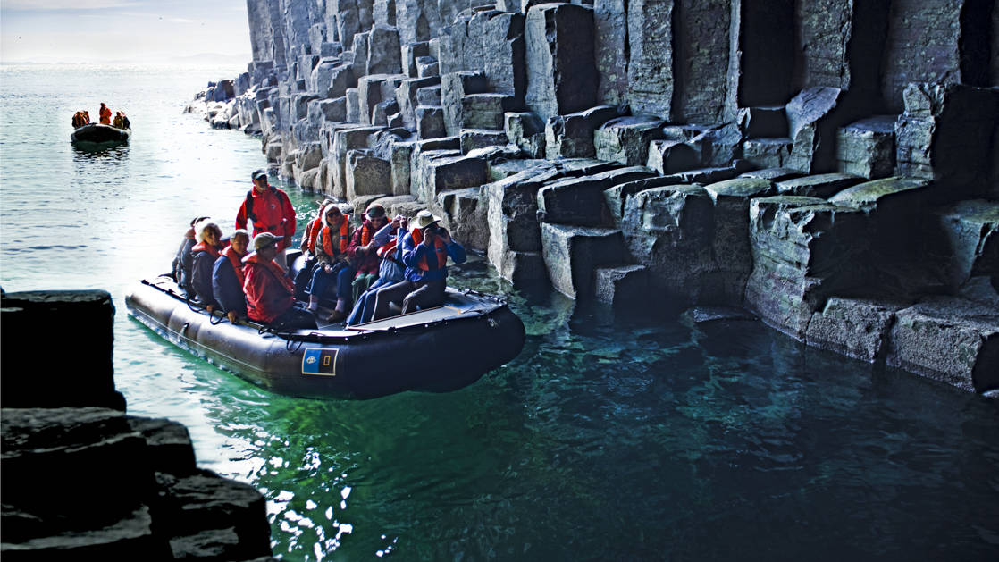 Guests explore Fingal's Cave, by Zodiac, on the uninhabited island of Staffa, in the Inner Hebrides of Scotland