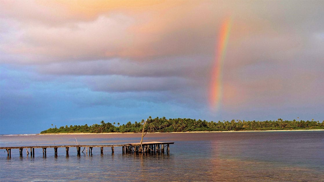 lone dock sticking out in the ocean in the pacific islands on a cloudy day with a vibrant rainbow in the distance