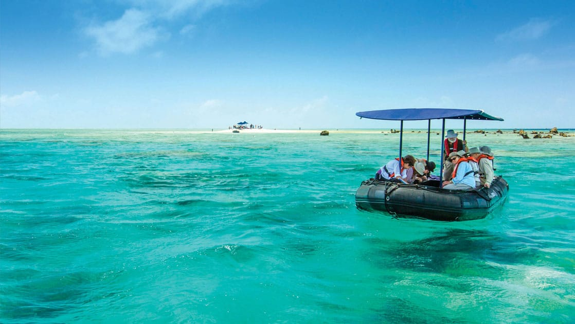 travelers on a covered zodiac skiff atop turquoise water of the pacific islands on a sunny day with a small white sand beach in the background