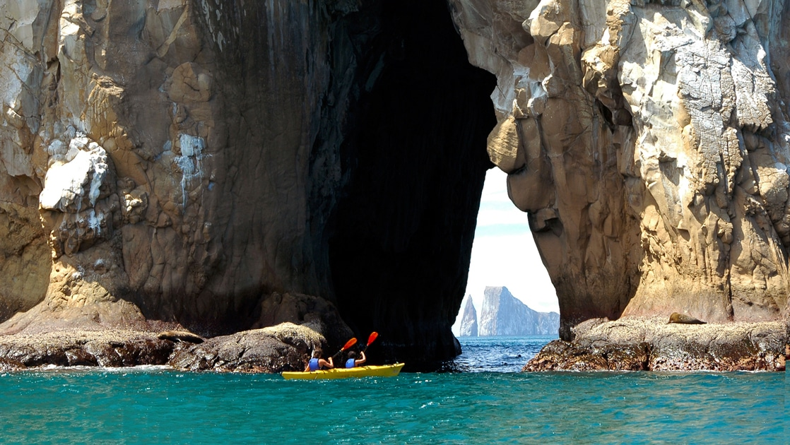 2 travelers paddle a yellow double kayak through the arch of a giant rock structure in the Galapagos, in the distance another iconic rock landmark, Kicker Rock.