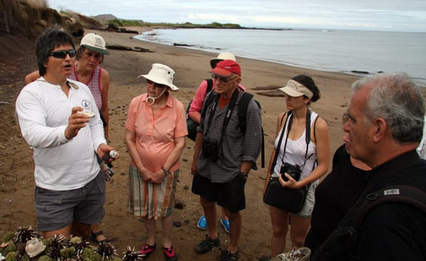 Galapagos travelers with a naturalist looking at tidal creatures.