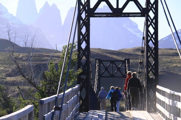 A group of tourist on a walking bridge with green hillsides and snowy mountains in Patagonia.