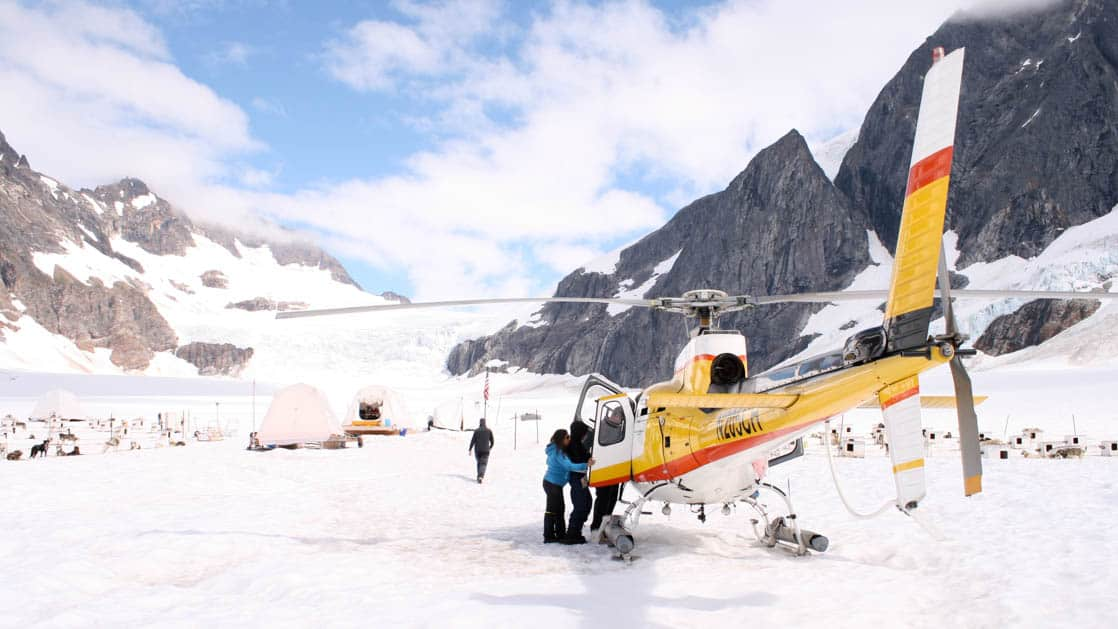 People getting out of a helicopter on top of a glacier next to a dog sledding camp in Alaska on a sunny day