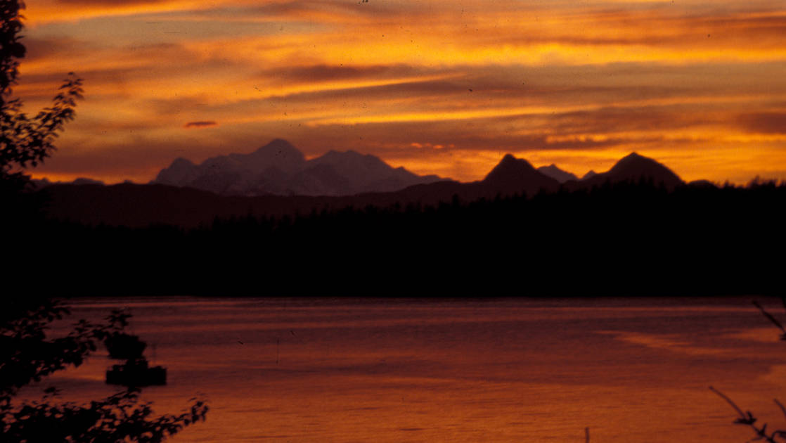 Orange sunset over the water with the silhouette of the fairweather mountains in southeast alaska