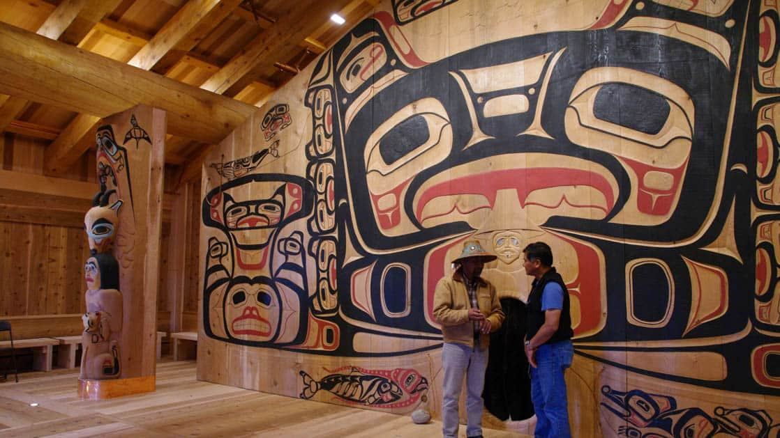 two men in a wooden tribal house with carvings and totem paintings in alaska