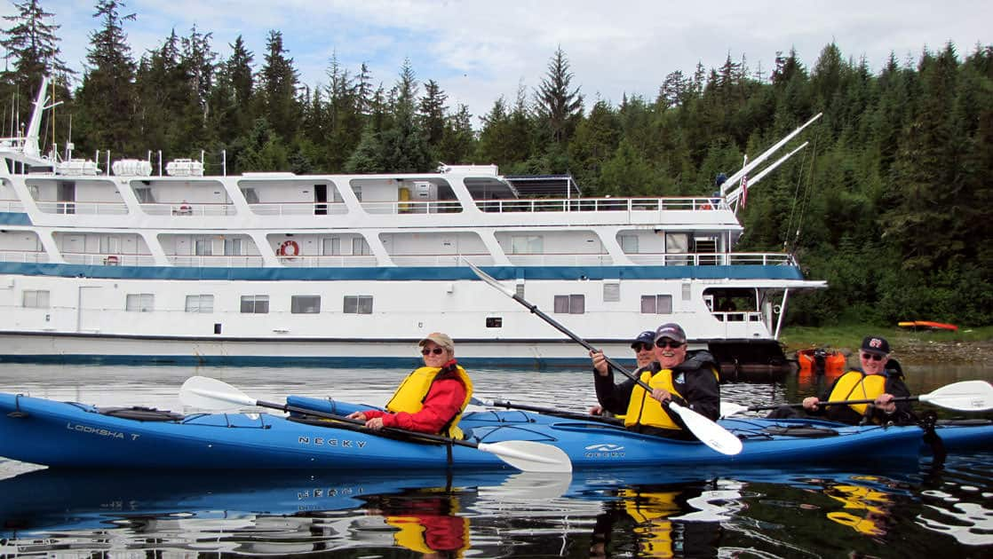 group of travelers in blue kayaks sit on glassy water with an alaska small ship behind them and a forest in the distance