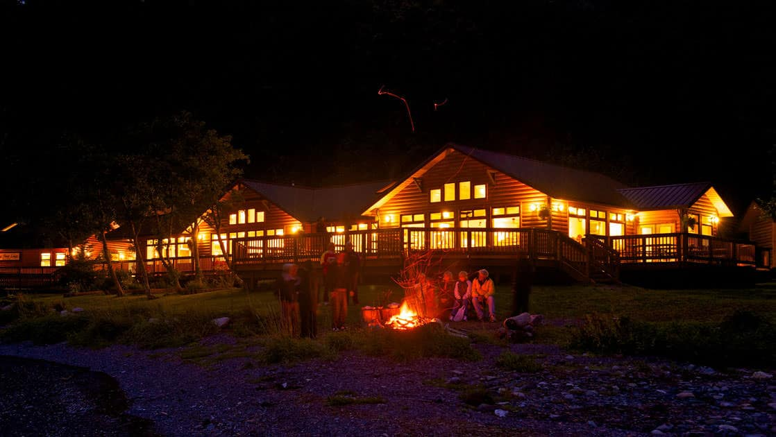 an illuminated orca point lodge at night with travelers standing around a fire in front of it in alaska