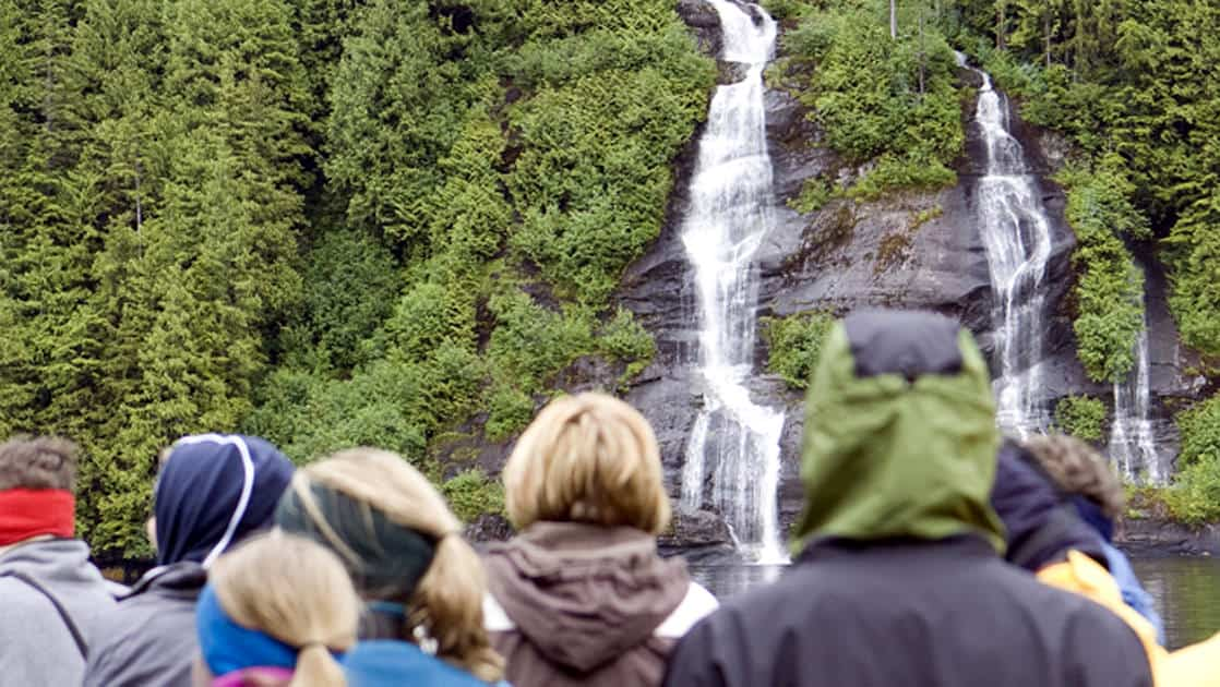 group of adventure travelers stand watching waterfalls come out of a grassy cliffside on an alaska hike