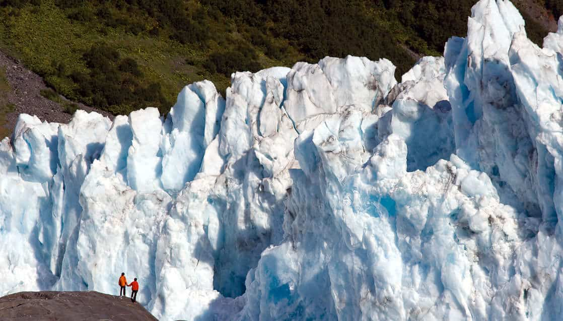 Two Hikers pause to view the massive tidewater face of Barry glacier, Prince William Sound, Alaska.