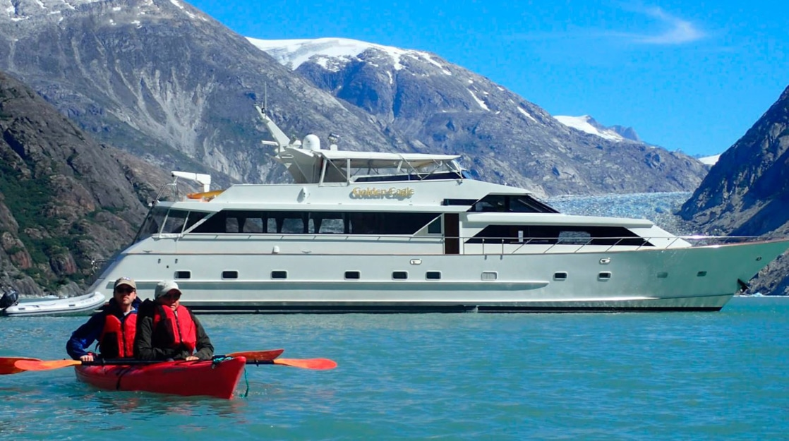 Two guests from the Golden Eagle yacht paddling in a double kayak in front of their small ship on a sunny day in Alaska.