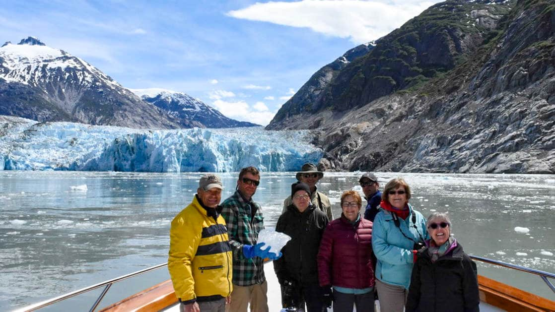 Group of adventure travelers on the bow of the Golden Eagle yacht with a glacier behind them on a sunny day in alaska.