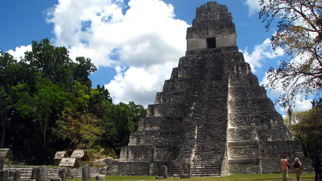A tikal multi-level pyramid with trees surrounding in Guatemala.