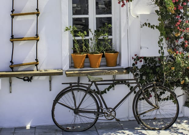 White buiding wall with window rope ladder, bougainvillea, potted plants and old townie bike.