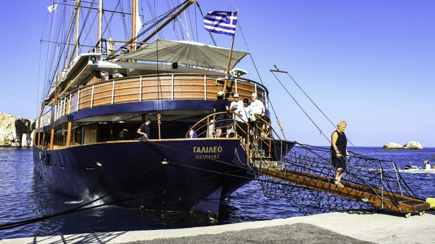 The small sail ship the Galileo docked with travelers disembarking off the boat in the Greek Isles.