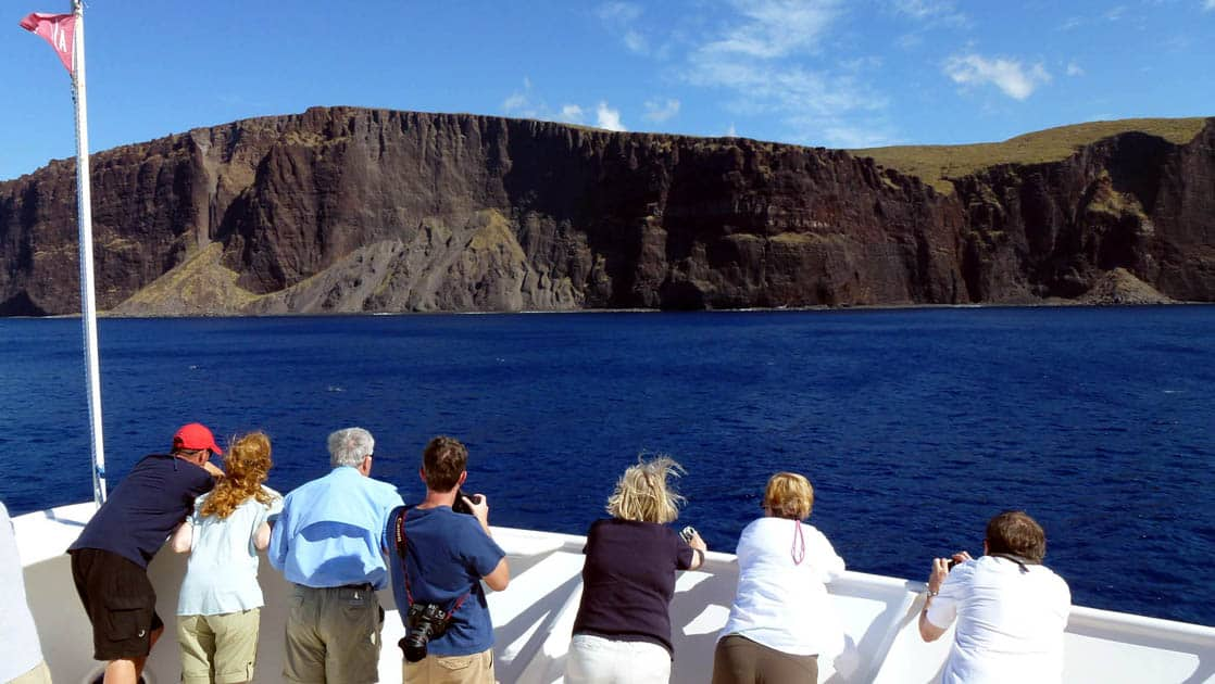 travelers look over the deck of the safari explorer small ship at the ocean and distant cliffs on a sunny day during the hawaiian seascapes cruise