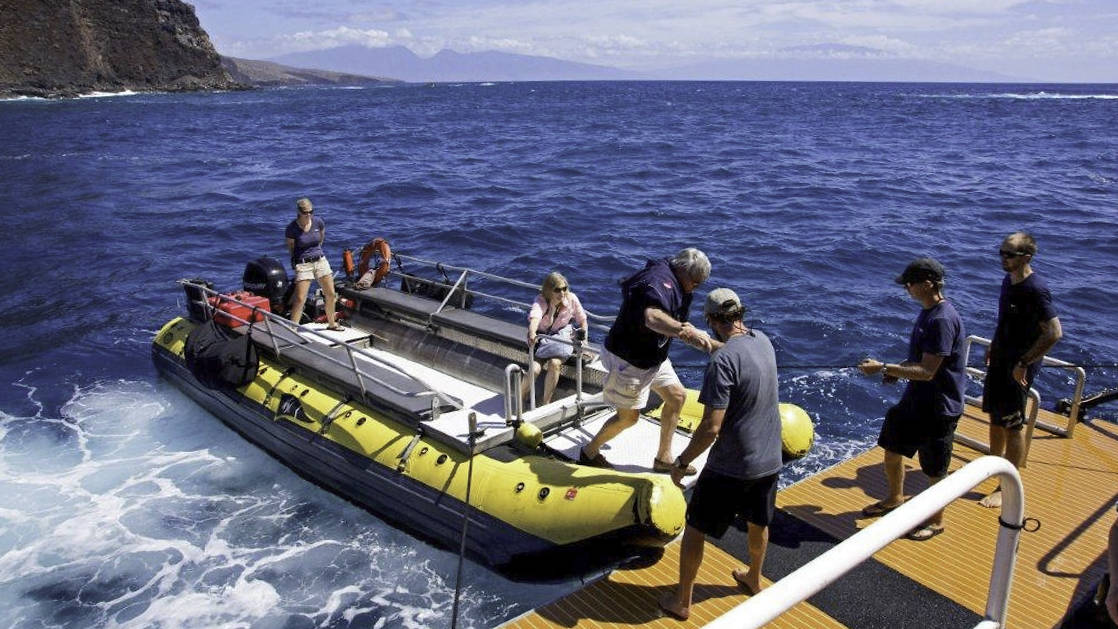 group of adventure travelers unload from a zodiac skiff onto the safari explorer hawaiian small ship on a sunny day