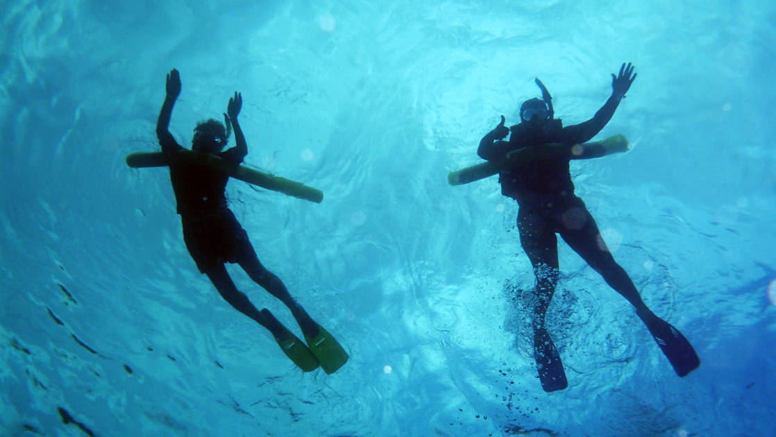 looking up at two travelers snorkel with crystalline blue water around them on the hawaiian seascapes small ship cruise