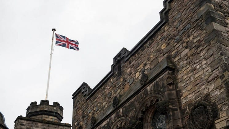 union jack flag flying over castle in scottish highlands