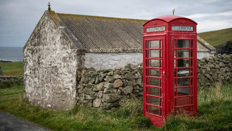 telephone booth beside stone house on from the highlands to the high arctic cruie