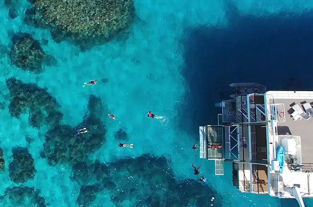 People snorkeling around a small ship above a reef in the Great Barrier Reef