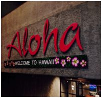 Aloha red sign that also says welcome to Hawaii with pink flowers