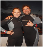 The two travelers in wetsuits at night excited for the night dive