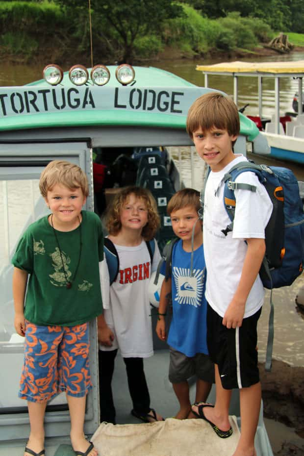 Group of young travelers embarking on a river boat in Costa Rica.