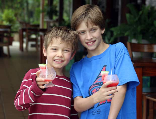 Young travelers enjoying a watermelon mocktail in Costa Rican lodge.