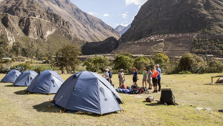 hikers set up tents at the bottom of incan ruins in peru