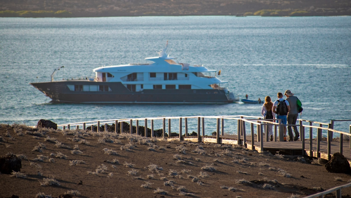 The Infinity Galapagos yacht floats off shore as cruise guests walk down a wooden ramp to get back on board after a shore excursion.