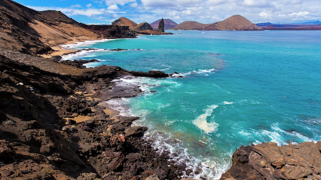 View from the top of hike on Bartolome island in the Galapagos, looking down on large rock formations that jet out from the teal ocean water.