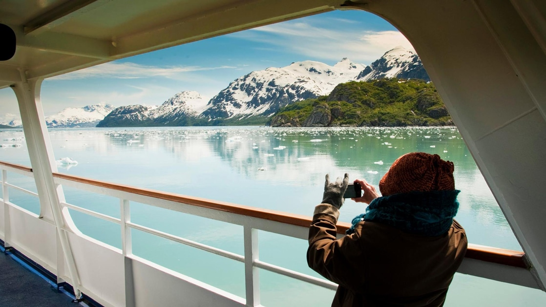 From the deck of a ship a guest holds a camera up to take a photo of the Alaska landscape while aboard Inside Passage Sojourn Alaska cruise.