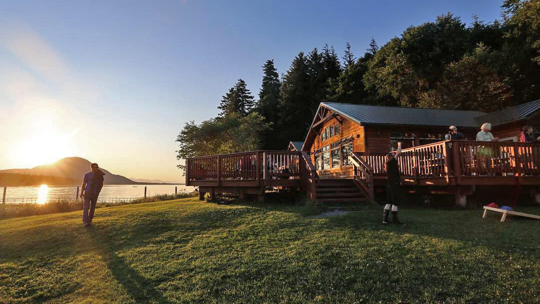 The sun is setting over the mountain range that surrounds the Orca Point lodge in Alaska as guests enjoy playing games on the lawn and patio.