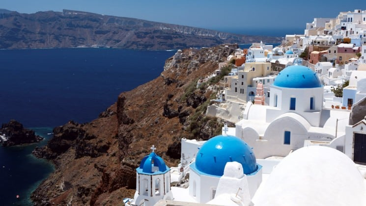 Aerial view of the white-stone buildings with blue-domed tops sitting on a hillside overlooking deep blue water in Santorini, Greece.