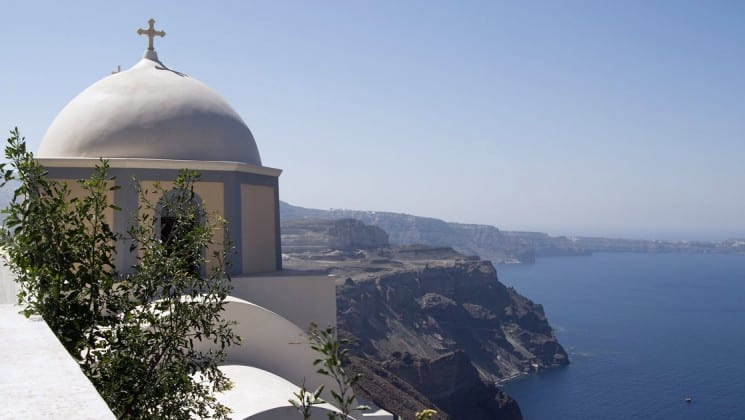 Dome-topped white stone building sits high above blue ocean in Santorini, Greece