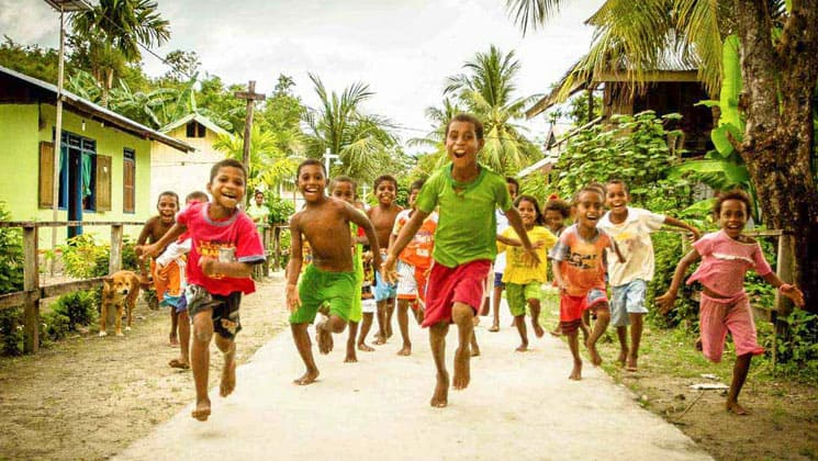 indigenous indonesian children in red and green clothing laughing and running at the camera with palm trees in the background