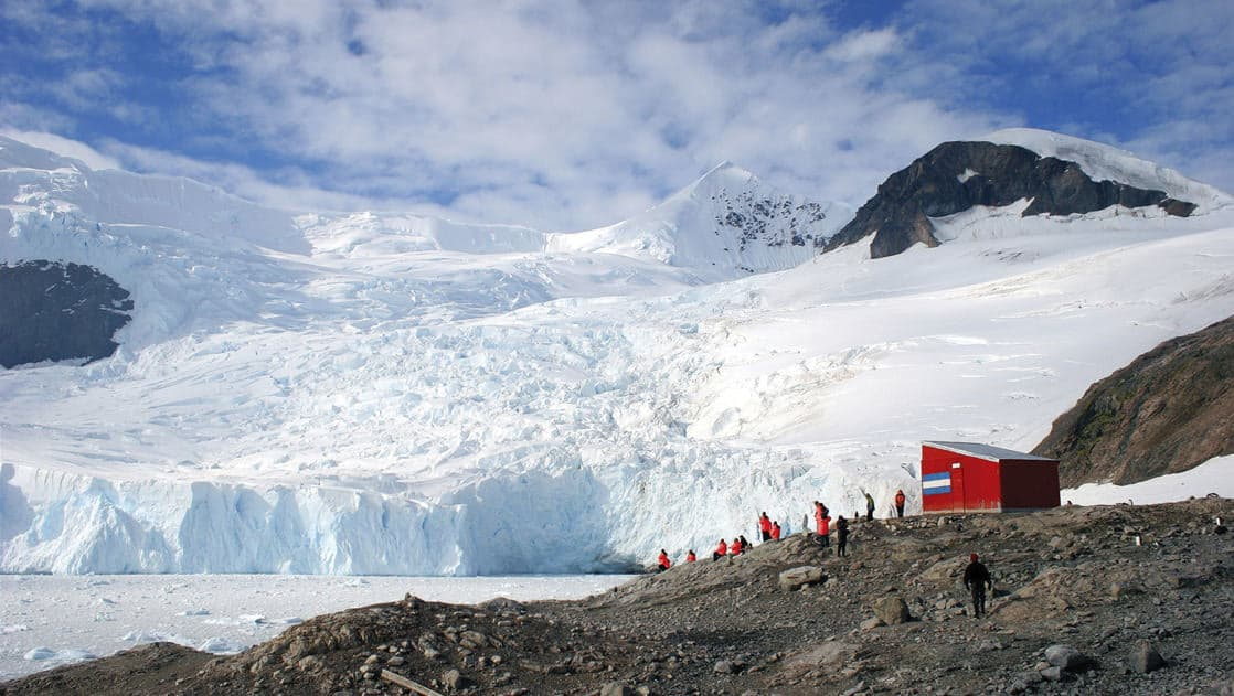 travelers hiking on an antarctica shore with a red hut next to them and a giant white iceberg behind them