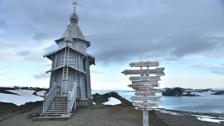 an old white church stands alone on an antarctica shoreline with a signpost in front of it and dark clouds above