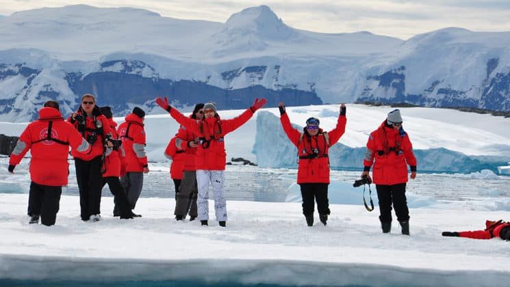 antarctica travelers in red jackets with their hands in the air standing on snow with a large mountain behind them