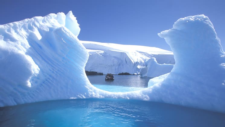 an illuminated antarctic iceberg in turquoise water on a sunny day with another larger iceberg behind it